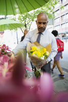 Businessman choosing flowers at sidewalk florist in city