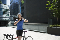 Woman adjusting bicycle helmet in sunny city