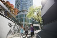 Runners on sunny city sidewalk