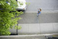 Woman with yoga mat on city sidewalk 11096029816| 写真素材・ストックフォト・画像・イラスト素材|アマナイメージズ
