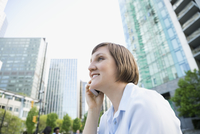 Businesswoman talking on cell phone below city highrise buildings