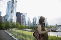 Pregnant businesswoman using cell phone on city boardwalk 11096029859| 写真素材・ストックフォト・画像・イラスト素材|アマナイメージズ