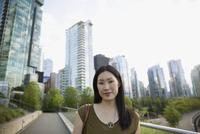 Portrait confident businesswoman on city boardwalk below highrise buildings