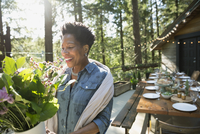 Smiling woman with bouquet of flowers on sunny cabin balcony in woods 11096029950| 写真素材・ストックフォト・画像・イラスト素材|アマナイメージズ