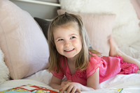 Smiling girl reading book laying on sofa