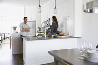 Couple drinking wine and cooking in kitchen