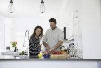Smiling couple drinking wine and cooking in kitchen