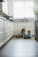 Brother and sister playing with pots and pans on kitchen floor 11096030466| 写真素材・ストックフォト・画像・イラスト素材|アマナイメージズ