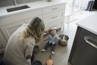 Playful mother and baby son playing with pots in kitchen
