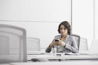 Businesswoman using cell phone in conference room 11096030571| 写真素材・ストックフォト・画像・イラスト素材|アマナイメージズ