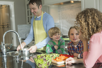 Family of four in kitchen as father prepares dinner. 11096030756| 写真素材・ストックフォト・画像・イラスト素材|アマナイメージズ