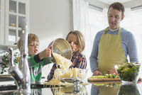 Father looking down as young son spills spaghetti outside bowl.