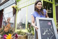 Female florist setting up open sign at flower shop 11096031040| 写真素材・ストックフォト・画像・イラスト素材|アマナイメージズ