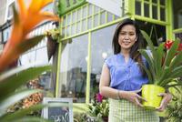 Portrait of female florist holding plant in front of flower shop 11096031269| 写真素材・ストックフォト・画像・イラスト素材|アマナイメージズ