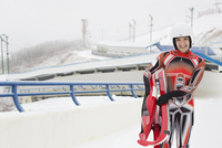 Portrait of female luge athlete holding sled by track