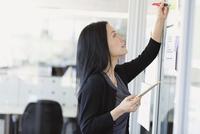 Businesswoman writing notes on project visuals in office 11096031580| 写真素材・ストックフォト・画像・イラスト素材|アマナイメージズ