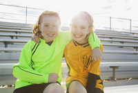 Portrait of soccer players sitting on bleachers