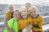 Portrait of cheerful soccer players on bleachers