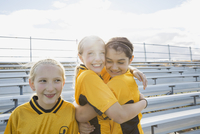 Soccer players hugging on bleachers