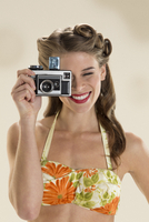 Pin-up girl using vintage camera