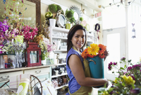 Portrait of female florist holding flowers at flower shop