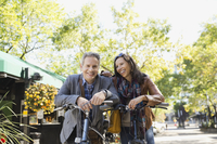 Happy couple with bicycles standing on street