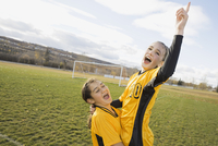 Cheerful soccer players celebrating success on field