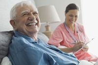 Senior man sitting with home care nurse