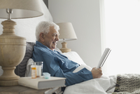 Senior home care patient sitting in bed reading