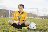 Portrait of confident soccer player holding trophy