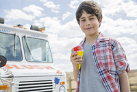 Portrait of cute boy holding ice cream outdoors
