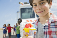 Close-up portrait of boy holding ice cream outdoors