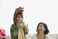 Boy in dragon costume laughing with mother