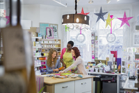Female small business owner teaching customers in store