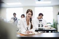 Portrait of female student writing notes in college science lab 11096033688| 写真素材・ストックフォト・画像・イラスト素材|アマナイメージズ
