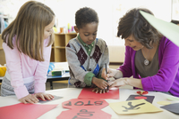 Students with teacher drawing road sign in art class