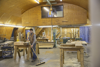 Carpenter sweeping sawdust with broom in workshop