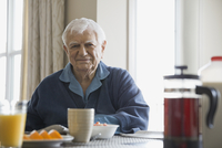 Portrait of smiling senior man sitting at breakfast table