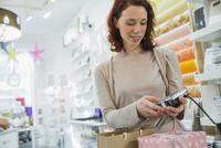Female customer entering PIN into PIN pad at store