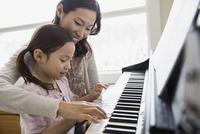 Mother teaching daughter to play piano 11096033967| 写真素材・ストックフォト・画像・イラスト素材|アマナイメージズ