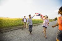 Cheerful friends running with American flag 11096034150| 写真素材・ストックフォト・画像・イラスト素材|アマナイメージズ