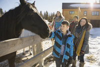 Family visiting horses on winter ranch