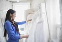 Young woman choosing wedding dress at bridal store