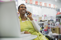 Female small business owner talking on phone in store