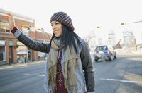 Woman hailing taxi on city street 11096034397| 写真素材・ストックフォト・画像・イラスト素材|アマナイメージズ