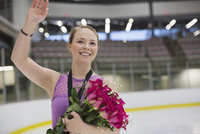 Smiling female figure skater with flowers in skating rink
