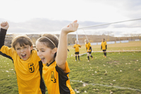 Soccer players celebrating success on field