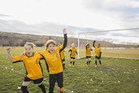 Cheerful soccer girls celebrating on field