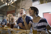 Friends watching TV and cheering at brewery