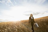 Businesswoman with briefcase walking through field 11096034755| 写真素材・ストックフォト・画像・イラスト素材|アマナイメージズ